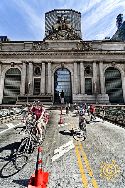 Bike Riders and other folks ride and walk by on the approach to Grand Central Station on NYC Streets Day.